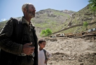A man and his son stare at the remains of their village (Dahan-e-Aab) after this was hit by a debris and mud flow in 2012
