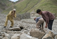 A father and his two boys crush stones in a landslide deposit. Selected stones will then be carried to the citie, to be sold as building material
