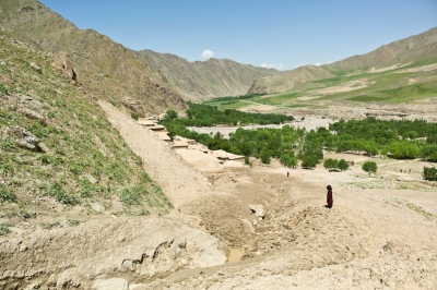 A little girl stands on the mud that now covers several houses at Dahan-e-Aab, after the event of spring 2012.