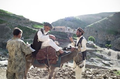 Two men receive a visitor from a nearby village