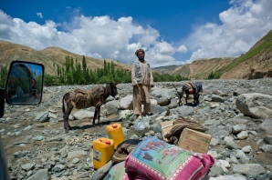 A traveler and his animals on a break by a river during a travel between villages